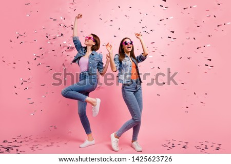 Full length body size photo beautiful she her sisters ladies festive hands raised listen playlist clubbing celebrate confetti fly fall wear jeans denim jackets blazers isolated bright pink background