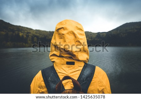 Active outdoors people lifestyle. Rear view of a hiker enjoying rainy weather. Outdoors adventure trek activity, hiker wearing yellow waterproof raincoat sportswear clothes #1425635078
