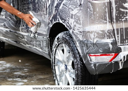 Manual car wash in car wash shop service with employee worker in back. #1425635444