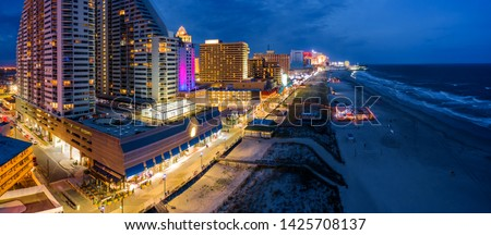 Aerial panorama of Atlantic city along the boardwalk at dusk. In the 1980s, Atlantic City achieved nationwide attention as a gambling resort and currently has nine large casinos. Royalty-Free Stock Photo #1425708137