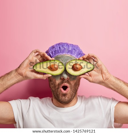 Vertical shot of surprised man holds avocado slices on eyes for skin care procedure, applies beauty clay mask, uses healing properties of fruit, feels fresh after healthy treatments, poses indoor Royalty-Free Stock Photo #1425769121