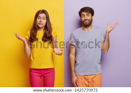 Indifferent unbothered woman and man spread hands sideways, have no idea, dressed in casual outfit, pose against different color background. Confused questioned couple with clueless expression indoor #1425770972