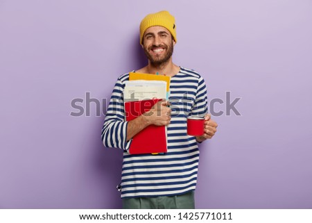 Happy college student carries papers and notepad, prepares for exams, drinks hot beverage from cup, wears striped clothing, isolated over purple wall, studies at high school. Education concept #1425771011