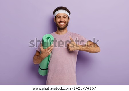 Glad unshaven man makes okay gesture, keeps thumb up, holds rolled up karemat, shows he liked yoga training wears casual t shirt in one tone with background. People, workout, healthy lifestyle concept #1425774167