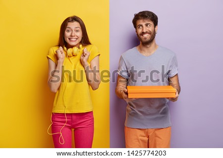Glad female clenches fists, wears headphones on neck, waits for present from boyfriend, happy man holds small gift box, makes surprise for woman. Couple pose against two colored studio wall. #1425774203