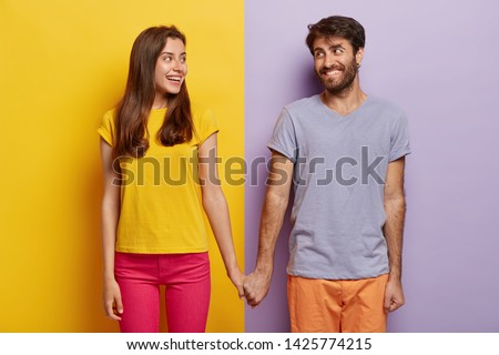 Romantic couple in love have date, hold hands, look positively at each other, feel support, walk together. Positive man poses over purple background, woman on yellow. Contrast. Relationship concept #1425774215