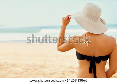 Skin care. Sun protection. Beauty Woman apply sun cream. Woman With Suntan Lotion On Beach In Form Of The Sun. Portrait Of Female With  Drawn Sun On A Shoulder. Suncream. Girl Holding  #1425843860