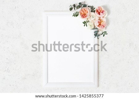 Wedding, birthday sign board mock-up scene. Vertical white wooden frame. Decorative floral corner. Eucalyptus, pink English roses and ranunculus flowers. Concrete table background. Flat lay, top view.