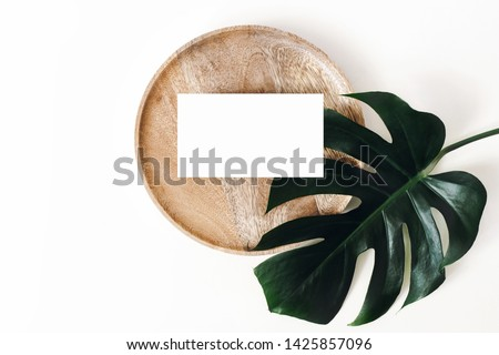 Tropical summer stationery mock-up scene. Blank business card, wooden tray, green monstera leaf isolated on white table background. Summer branding styled photo, web banner. Flat lay, top view