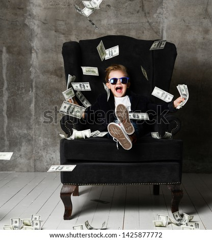 Happy and shoutting arrogant rich kid boy millionaire sits with a bundle of money dollars cash in big luxury armchair while bills falling down from the sky. Money rain