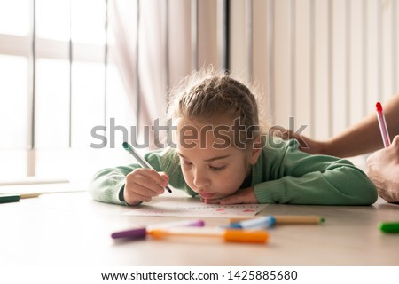 Serious lazy pretty girl with braided hair lying on floor and coloring picture with felt-tip pens while her father supporting her creativity and stroking her back