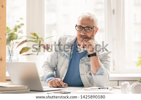 Mature pensive businessman in casualwear looking at you while sitting by desk in front of laptop in office #1425890180