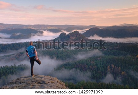 Man in warm jacket with backpack in spring rockx mountains. Travel concept. #1425971099