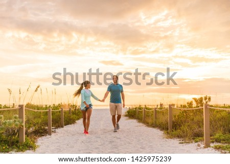 Happy young couple in love walking on romantic beach stroll at sunset. Lovers holding hands on Florida vacation holidays. People walking on summer evening lifestyle. #1425975239