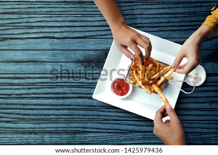 Three Friends Eating French Potato Fries, Serve on Metal Mesh Flying Sieve with Two Dipping Sauce. Lay on Wooden Table. High Angle Top View Shot #1425979436