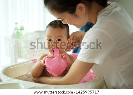 Asian beautiful mother holding little cute baby and taking a bath her child sitting in bathtub in the room. Bathtub and bath shampoo are put in the background. Clean and healthy concept. #1425995717