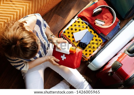Upper view of modern woman in white pants and striped blouse at modern home in sunny summer day packing first aid kit and SPF in open travel suitcase. #1426005965