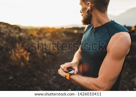Athletic runner start training on fitness tracker or smart watch and looking forward on horizon. Trail running and active lifestyle concept. #1426010411