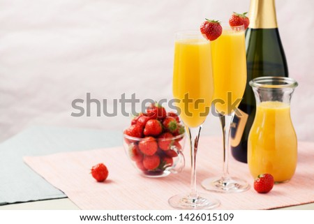 Two glasses of mimosa cocktail (champagne with orange juice) and fresh strawberries #1426015109