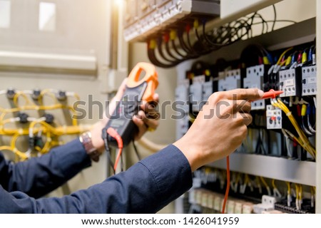 Electrician engineer work  tester measuring  voltage and current of power electric line in electical cabinet control. #1426041959