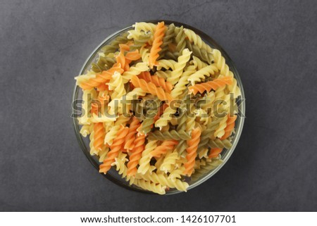 A bowl with uncooked pasta fusilli tricolor #1426107701