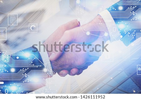 Close up of two businessmen shaking hands over blurred skyscraper background with double exposure of electronic brain hologram. Concept of AI and hi tech start up. Toned image