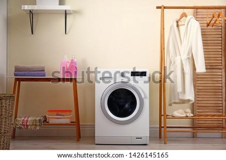 Laundry room interior with modern washing machine #1426145165
