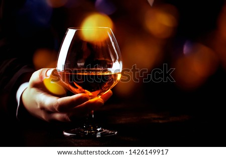 French glowing cognac glass in hand on the dark bar counter background, copy space, selective focus Royalty-Free Stock Photo #1426149917