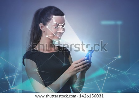 Smiling young woman with smartphone. Face recognition and biometric verification interface, network hologram. Concept of cyber security and AI. Toned image double exposure #1426156031