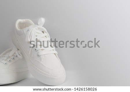 New white female or teen sneakers on gray background. White textile shoes with rubber soles and tied laces on a light gray background. Use for banners, promotional flyers