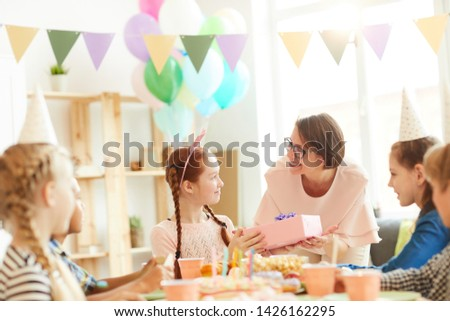 Multi ethnic group of children celebrating birthday sitting at table in cafe, focus on mother giving present to daughter, copy space #1426162295