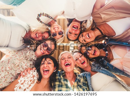 Group of beautiful people in friendship enjoying the party outside on the terrace. Large smiles for the photo from below. Nine women together