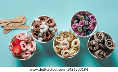 rolled ice creams in cone cups on blue background. Different iced rolls top view or flat lay. Thai style rolled ice cream #1426203194