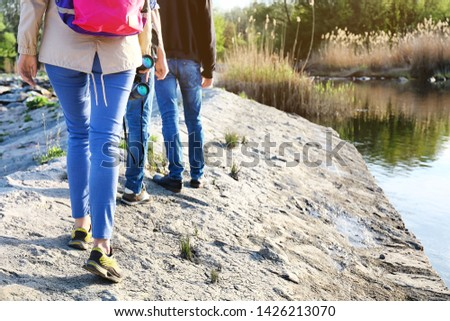Group of tourists walking near river #1426213070