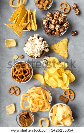 Assortment of Unhealthy Snacks: chips, popcorn, nachos, pretzels, onion rings in bowls, top view, flat lay. Unhealthy eating concept. Royalty-Free Stock Photo #1426235354
