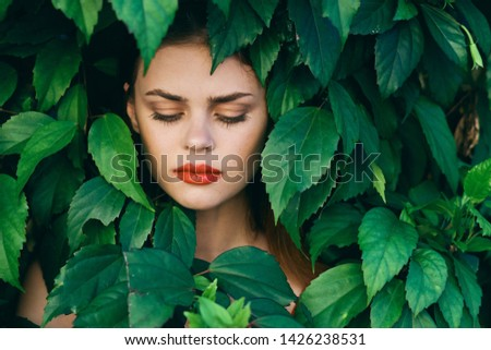 The game is a gorgeous female model with makeup and with closed eyes and green bushes leaves the park                            #1426238531