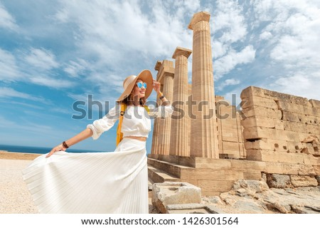 Happy asian Traveler with backpack walking in historical and archaeological site in Lindos Acropolis. Tourist attraction and ancient architecture in Greece #1426301564