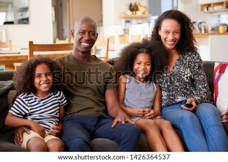 Portrait Of Smiling Family Sitting On Sofa At Home Relaxing Together #1426364537
