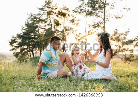 happy family concept - father, mother and child daughter having fun and playing in nature. #1426368953