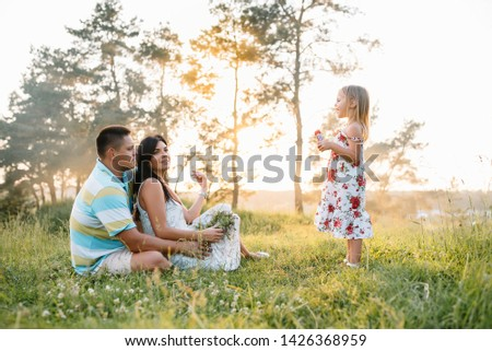happy family concept - father, mother and child daughter having fun and playing in nature. #1426368959