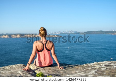 Morning view of a young female hiker sitting on a rock at North Head, a headland in Manly and part of Sydney Harbour National Park in Sydney, New South Wales, Australia. Sydney skyline in background. Royalty-Free Stock Photo #1426477283
