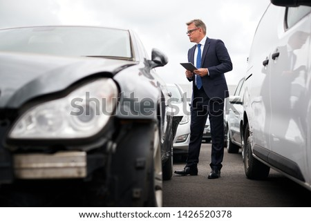 Male Insurance Loss Adjuster With Digital Tablet Inspecting Damage To Car From Motor Accident #1426520378