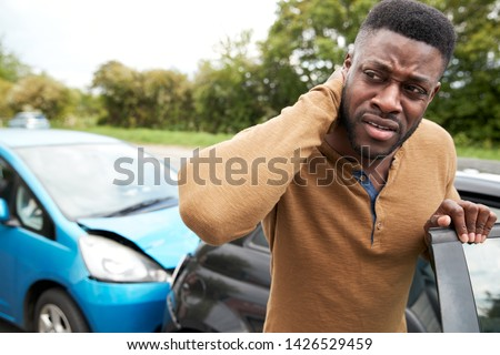 Male Motorist With Whiplash Injury In Car Crash Getting Out Of Vehicle Royalty-Free Stock Photo #1426529459
