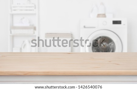 Wooden table in front of defocused washing machine and laundry #1426540076