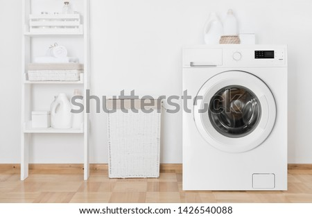 Interior of home laundry room with washing machine near wall #1426540088