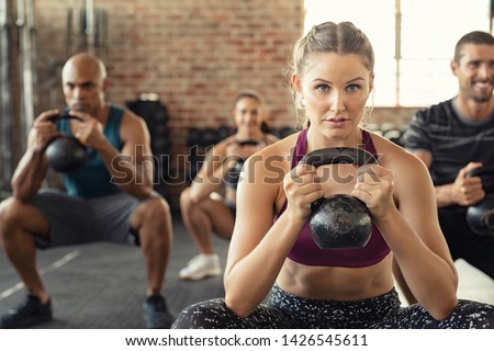 Group of fit people holding kettle bell during squatting exercise at gym. Fitness girl and men lifting kettlebell during strength training exercising. Young people doing squat with heavy kettlebells. #1426545611