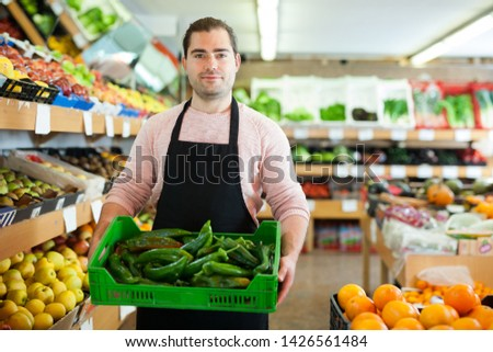 Young male seller standing with box of green pepper on the supermarket #1426561484