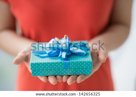 Close-up of female hands holding a present Royalty-Free Stock Photo #142656325