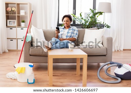household and technology concept - happy african american woman or housewife with smartphone resting after home cleaning #1426606697