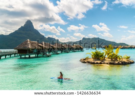 Tahiti luxury resort hotel in Bora Bora ,French Polynesia. Paddleboard leisure activity SUP paddle woman on active vacation in Tahiti, French Polynesia. Mount Otemanu summer holiday. #1426636634